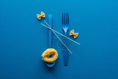 Photo for Vermicelli pasta on blue plastic spoon with spaghetti on fork and spoon near farfalle pasta on blue background - Royalty Free Image