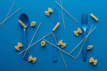 Photo pour Couverts en plastique bleu avec spaghettis non cuits autour et différents types de pâtes sur fond bleu - image libre de droit