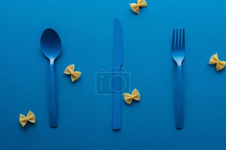 Photo for Blue plastic spoon, knife and fork with uncooked farfalle pasta around on blue background - Royalty Free Image