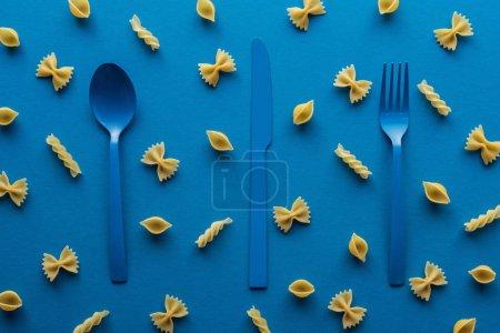 Photo pour Couverts en plastique bleu avec des pâtes non cuites autour sur le fond bleu - image libre de droit