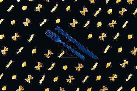 Photo pour Pose plate de différents types de pâtes avec fourchette bleue en plastique et couteau au milieu isolé sur noir - image libre de droit