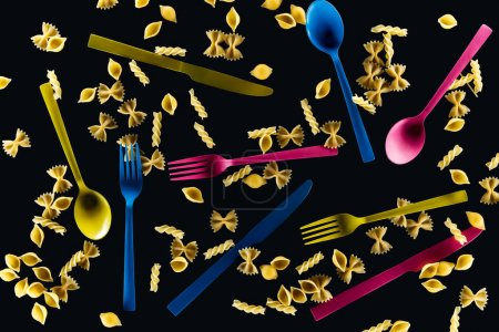Photo for Top view of mixed colorful knives, forks and spoons with different kinds of pasta isolated on black - Royalty Free Image
