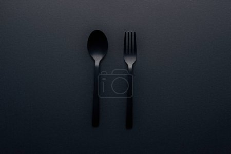 Photo for Top view of plastic spoon and fork on black background - Royalty Free Image