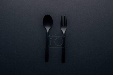 Photo pour Vue du dessus de la cuillère et de la fourchette en plastique sur fond noir - image libre de droit