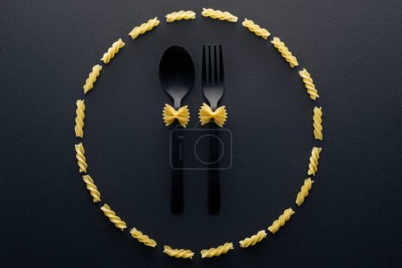 Photo for Top view of farfalle pasta on spoon and fork in circle from rotini pasta - Royalty Free Image