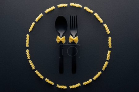 Photo pour Vue du haut des pâtes farfalle sur la cuillère et la fourchette en cercle des pâtes rotini - image libre de droit