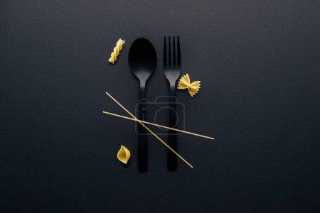 Photo pour Cuillère en plastique noir, fourchette et quatre différents types de pâtes sur fond noir - image libre de droit