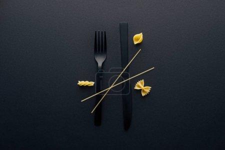 Photo pour Couteau en plastique noir à l'envers, fourchette et quatre différents types de pâtes sur fond noir - image libre de droit