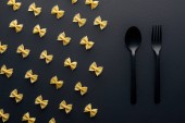 "Постер, картина, фотообои ""flat lay of farfalle pasta near plastic spoon and fork on black background"""