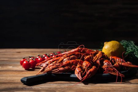 Photo for Red lobsters, tomatoes, dill and lemon on wooden surface - Royalty Free Image