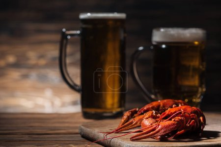 Photo for Selective focus of red lobsters and glasses with beer on wooden surface - Royalty Free Image