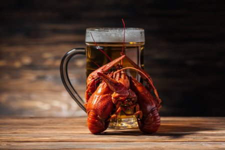Photo for Glass with beer and red lobsters on wooden surface - Royalty Free Image