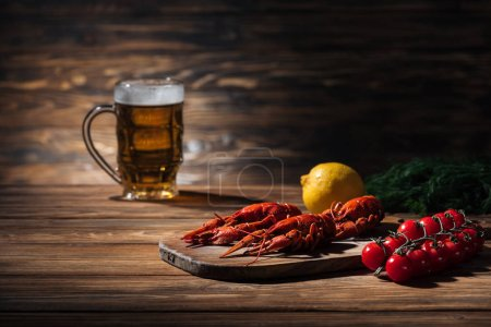 Photo for Red lobsters, tomatoes, dill, lemon and glass with beer on wooden surface - Royalty Free Image