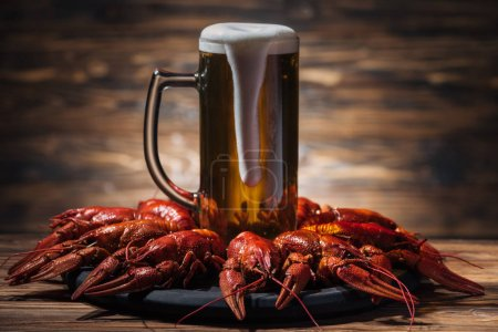 Photo for Glass with beer and foam on plate with red lobsters at wooden surface - Royalty Free Image