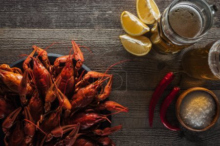 Photo for Top view of red lobsters, lemon slices, peppers, glasses with beer and salt on wooden surface - Royalty Free Image