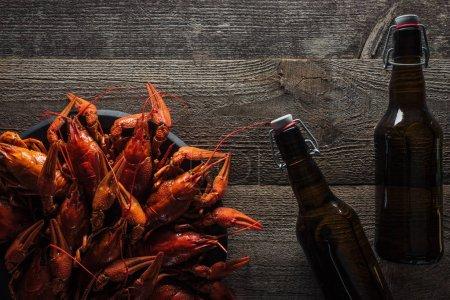 Photo pour Vue supérieure des bouteilles en verre et des homards rouges sur l'assiette à la surface en bois - image libre de droit