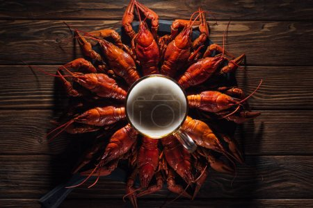 Photo for Top view of glass of beer on plate with red lobsters at wooden surface - Royalty Free Image