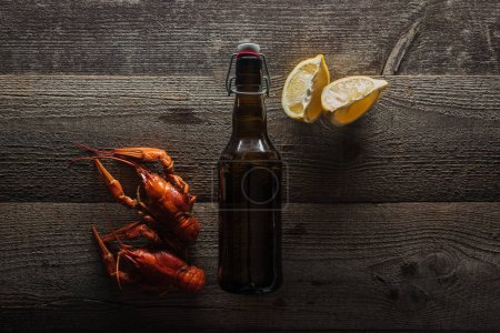 Photo for Top view of red lobsters, lemon slices and bottle with beer on wooden surface - Royalty Free Image
