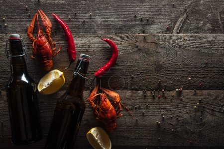 Photo for Top view of red lobsters, lemon slices, pepper and bottles with beer on wooden surface - Royalty Free Image