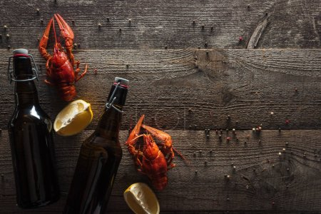 Photo for Top view of red lobsters, lemon slices and bottles with beer on wooden surface - Royalty Free Image