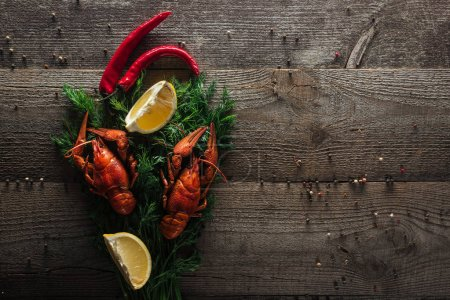 Photo for Top view of red lobsters, lemon slices, pepper and dill on wooden surface - Royalty Free Image