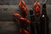 """Постер, картина, фотообои """"top view of red lobsters and bottles with beer on wooden surface"""""""