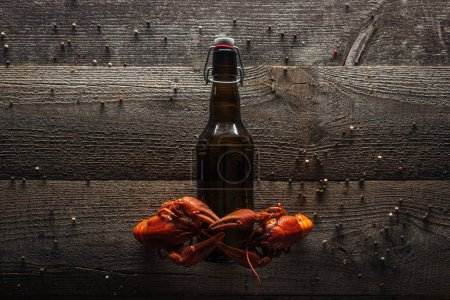 Photo for Top view of red lobsters on bottle with beer at wooden surface - Royalty Free Image