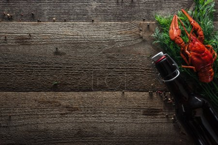 Photo for Top view of red lobster, dill and bottle with beer on wooden surface - Royalty Free Image