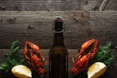 """Постер, картина, фотообои """"top view of red lobsters, dill, lemon slices and bottle with beer on wooden surface"""""""