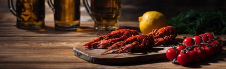 Photo for Panoramic shot of red lobsters, tomatoes, dill, lemon and glasses with beer on wooden surface - Royalty Free Image