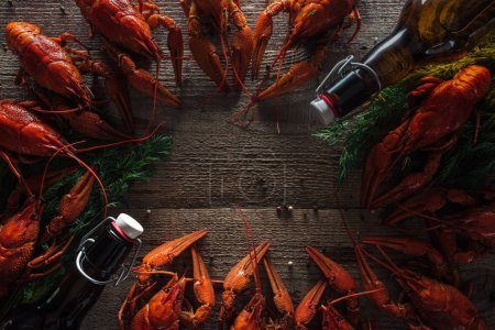 Photo for Top view of red lobsters, dill and glass bottles with beer on wooden surface - Royalty Free Image