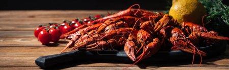 Photo pour Coup panoramique de homards rouges, aneth, citron et tomates sur la surface en bois - image libre de droit