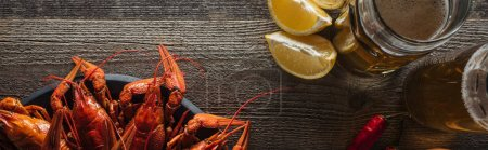 Photo for Panoramic shot of red lobsters, lemon slices, peppers and glasses with beer on wooden surface - Royalty Free Image