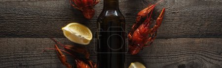 Photo for Panoramic shot of red lobsters, lemon slices and glass bottle with beer on wooden surface - Royalty Free Image