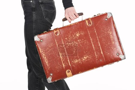 Photo pour Cropped view of girl in jeans holding vintage weathered suitcase isolated on white - image libre de droit