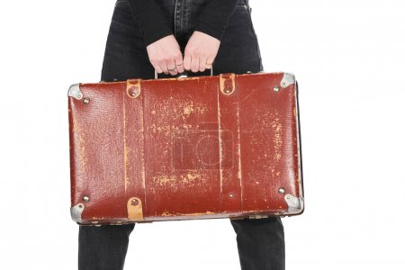 Photo pour Cropped view of girl in jeans holding vintage suitcase isolated on white - image libre de droit