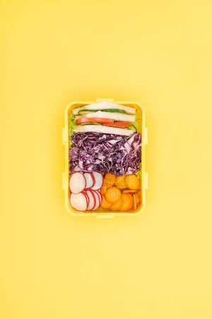 Photo for Top view of lunch box with sandwiches and vegetables on yellow background - Royalty Free Image