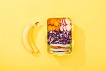 Photo for Top view of lunch box with sandwiches and vegetables near bananas - Royalty Free Image