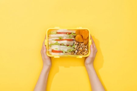 Photo for Cropped view of woman holding lunch box with nuts, dried apricots and sandwiches in woman hands - Royalty Free Image