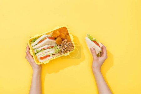 Photo for Cropped view of lunch box with nuts, dried apricots and sandwiches in woman hands - Royalty Free Image
