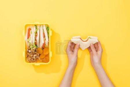 Photo for Cropped view of woman hold sandwich near lunch box with nuts, dried apricots and snacks - Royalty Free Image