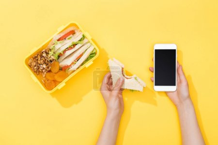Photo for Cropped view of woman holding sandwich and smartphone near lunch box with food - Royalty Free Image