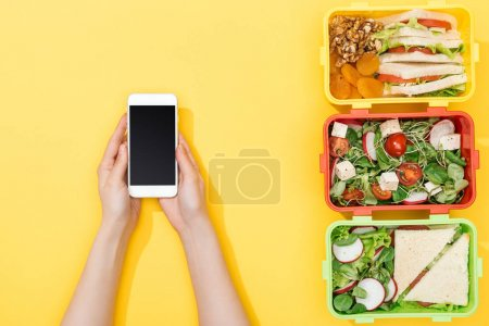 Photo for Cropped view of woman holding smartphone near lunch boxes with food - Royalty Free Image