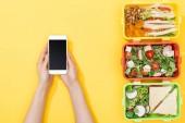"""Постер, картина, фотообои """"обрезанный вид женщины, держащей смартфон возле коробки с едой"""""""