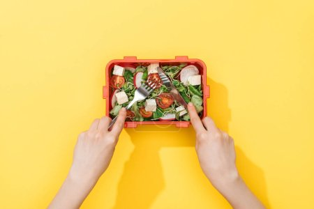 Photo for Cropped view of woman holding fork and knife, eating salad from lunch box - Royalty Free Image