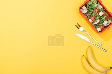 Photo for Top view of bananas, fork and knife near lunch box with salad - Royalty Free Image