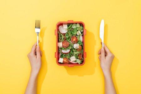 Photo pour Vue recadrée de fourche et de couteau de fixation de femme au-dessus de la boîte de déjeuner avec la salade - image libre de droit