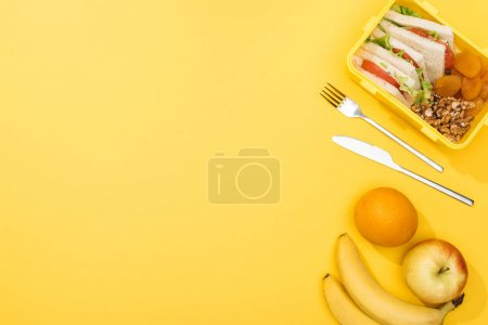 Photo for Top view of lunch box with sandwiches, nuts, dried apricots, near fork, knife, oranges and bananas - Royalty Free Image