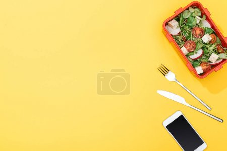 Photo for Top view of lunch box with salad near fork, knife and smartphone - Royalty Free Image