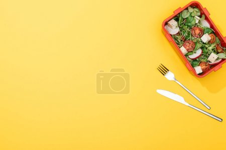 Photo for Top view of lunch box with salad near fork and knife - Royalty Free Image